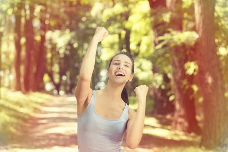 mujeres felices: Retrato ajuste corredor de fitness femenino alegre y emocionado despu�s de correr. Mujer de bombeo de los pu�os. �xito en el concepto de bienestar entrenamiento deportivo. Expresi�n de la cara positiva emoci�n