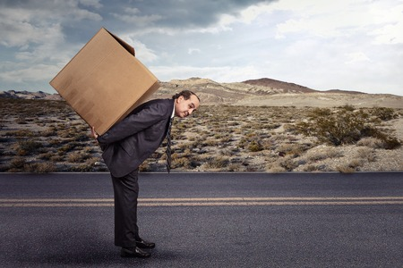 moving box: Man carrying large carton box on his back on a remote countryside road. Delivery, shipping, moving goods concept