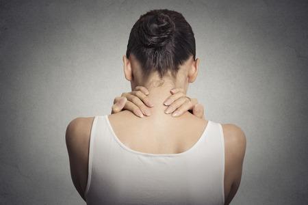 Gezonde levensstijl arbeidsomstandigheden. Rug en wervelkolom ziekte. De close-up terug bekijken vermoeide vrouw masseert haar pijnlijke nek op een grijze muur achtergrond