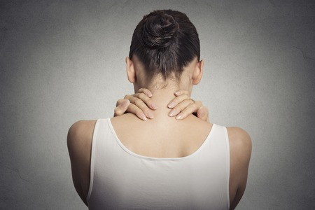 Healthy lifestyle working conditions. Back and spine disease. Closeup back view tired female massaging her painful neck isolated on gray wall background Foto de archivo