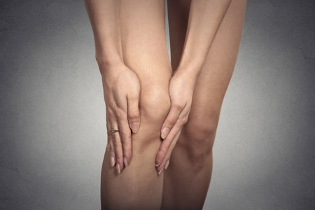 degenerative: Tendon knee joint problems closeup cropped image woman leg isolated on gray wall background. Joint trauma concept