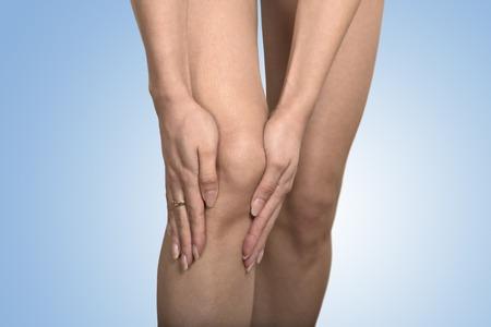 luxacion: Rodilla tend�n problemas en las articulaciones. Primer cosechado mujer imagen manos tocando la rodilla de la pierna dolorosa aisladas sobre fondo azul. Concepto de inflamaci�n de las articulaciones. Foto de archivo