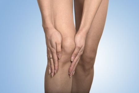 degenerative: Tendon knee joint problems. Closeup cropped image woman hands touching painful leg knee isolated on blue background. Joint inflammation concept.