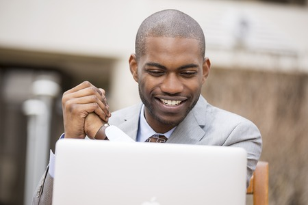 american media: Happy smiling handsome business man with laptop computer sitting outdoors Stock Photo