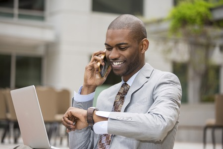 african business man: Closeup handsome young businessman working with laptop outdoors talking on mobile phone looking at his wristwatch. Time is money Stock Photo