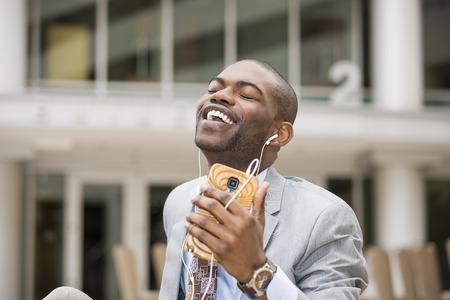 oido: Disfrutando el ritmo de su vida. Primer del hombre joven y guapo sonriendo mientras escucha m�sica Foto de archivo