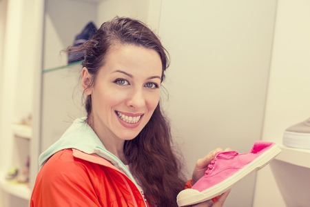 comfortable: Young happy casual woman shopping at footwear store holding pair of comfortable walking shoes