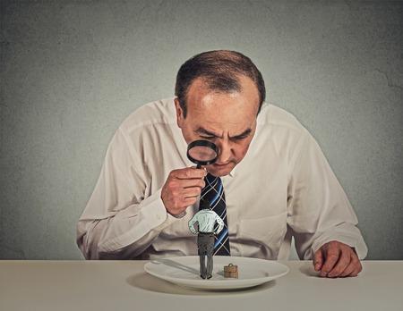 supervisión: Curioso el hombre de negocios corporativos de reuniones con escepticismo mirando pequeño empleado través de la lupa de pie sobre la mesa aislada plato de fondo gris de la pared. Rostro humano percepción actitud expresión