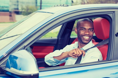 new rules: Car driver young man wearing safety belt driving new blue car in summer. Happy male looking at camera.