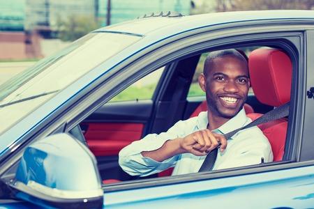 hombre conduciendo: Hombre joven conductor del coche que llevaba cinturón de seguridad al conducir el nuevo coche azul en verano. Masculino feliz mirando a la cámara.