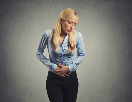 irritable bowel syndrome: woman suffering from severe pain in her tummy isolated on gray wall background Stock Photo