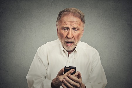 funny elderly: Closeup portrait, funny elderly man, shocked surprised with wide open mouth, by what he sees on his cell phone isolated on gray wall background