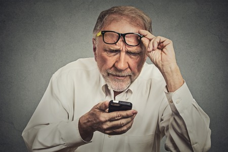 examen de la vista: Headshot Retrato del primer hombre mayor con gafas que tiene problemas para ver teléfono celular tiene problemas de visión. Mensaje de texto Bad. Negativo emoción humana percepción expresión facial. Tecnología Confundir