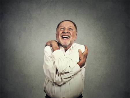 hug: Closeup portrait confident smiling man holding hugging himself isolated on grey wall background. Stock Photo