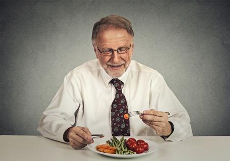 man eating: Happy senior man eating fresh vegetable salad