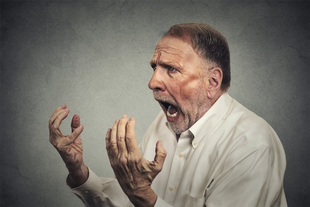 hands on head: Side profile portrait of senior angry man