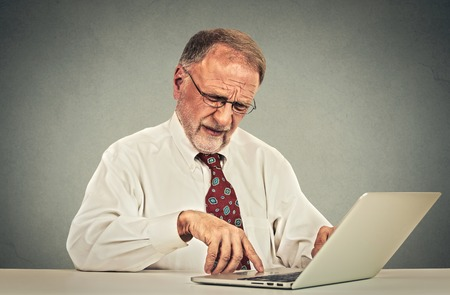 Confused looking elderly mature man with glasses sitting at table working typing on laptop computer
