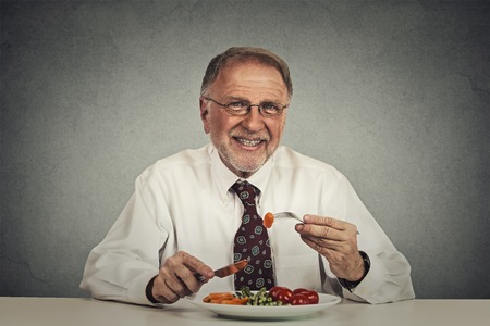 relaxed man: Happy senior man eating fresh vegetable salad