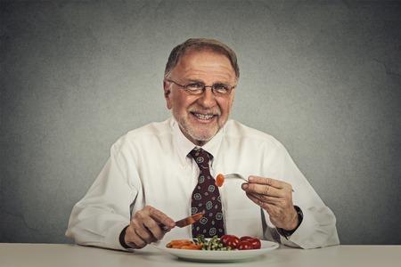 white man: Happy senior man eating fresh vegetable salad