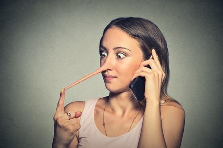 nariz: Conmocionado mujer con la nariz larga hablando por teléfono móvil aislado en el fondo de la pared gris. Foto de archivo