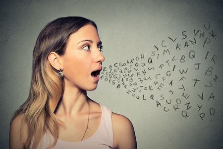 communication: Une femme parle avec des lettres de l'alphabet qui sort de sa bouche. Banque d'images