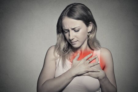 nude young woman: sick woman with heart attack, pain, health problem holding touching her chest colored in red with hands isolated on gray wall background.  Stock Photo