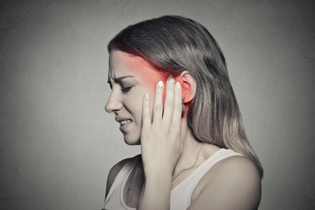 listening ear: Closeup up side profile sick female having ear pain touching her painful head temple isolated on gray wall background Stock Photo