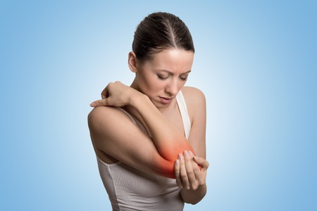elbow: Joint inflammation indicated with red spot on females elbow.