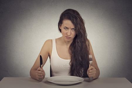 Jonge sceptische dieet vrouw moe van het dieet beperkingen kijken camera aan tafel zitten met lege plaat met vork en mes. Stockfoto