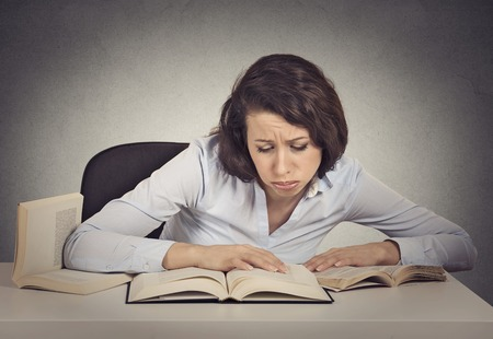 too much work: Portrait young woman student with desperate expression looking at her books, too much work to do Stock Photo