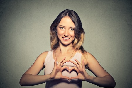 cholesterol: Closeup portrait smiling cheerful happy young woman making heart sign with hands isolated grey wall background.  Stock Photo
