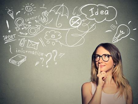 mujer pensando: Retrato de jóvenes felices sueños mujer de pensamiento tiene muchas ideas mirando hacia arriba aislados fondo de la pared gris. Foto de archivo