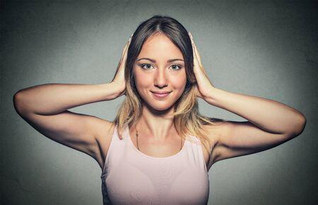 oido: Retrato de joven y atractiva mujer feliz que cubre con las manos los o�dos aislados sobre fondo gris de la pared.