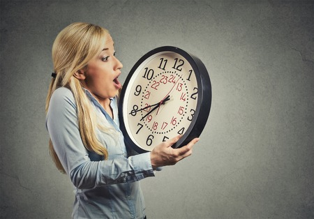 Closeup portrait woman worker holding clock looking anxiously