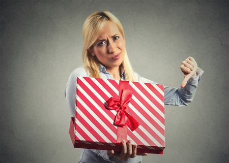 inappropriate: Closeup portrait young woman holding opening gift box displeased Stock Photo