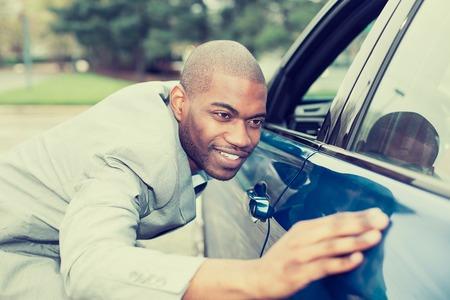 興奮した若い男と彼の新しい車