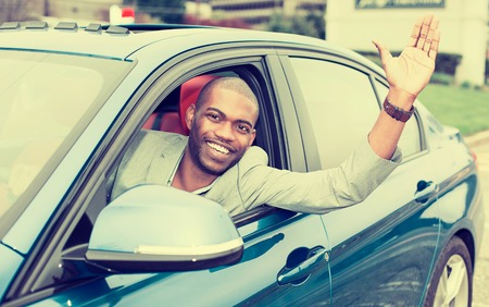 black car: Portrait happy young man driver stuck his hand out of the car window excited about his new blue car Stock Photo