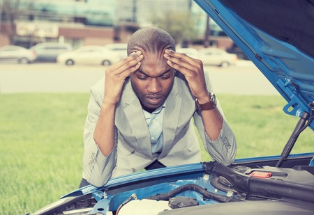 fail: young stressed man having trouble with his broken car looking in frustration on failed engine