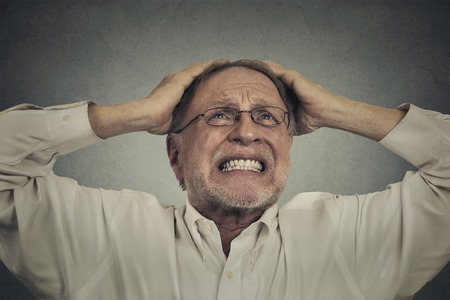 pissed off: Closeup portrait headshot furious frustrated elderly man having bad hard day screaming looking up isolated on gray wall background. Negative face expression emotion Stock Photo
