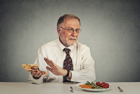 cravings: Senior man eating fresh vegetable salad avoiding fatty pizza