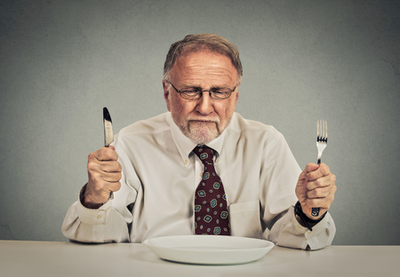 dissect: Serious elderly businessman with empty plate knife and fork ready
