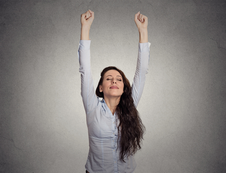 relief: attractive happy businesswoman with her arms raised on gray wall background