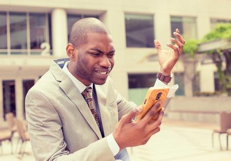 decepcionado: Frustrado joven hombre de negocios en traje de recibir malas noticias mensaje en el teléfono móvil inteligente de pie al aire libre fuera de la oficina corporativa