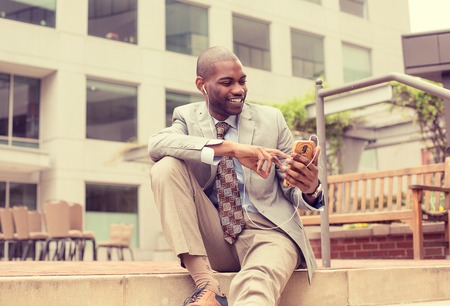 phone business: Young happy smiling urban professional man using smart phone listening to music.  Stock Photo