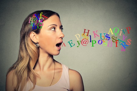 Side view portrait woman talking with alphabet letters in her head and coming out of her open mouth isolated grey wall background. Foto de archivo