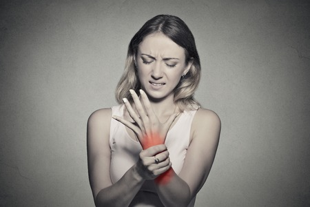 Young woman holding her painful wrist isolated on gray wall background.  Foto de archivo