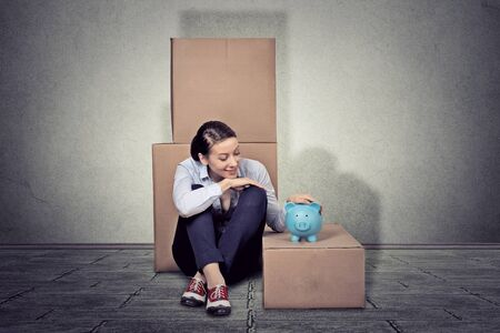 sales bank: Portrait young happy woman sitting on the floor with many boxes, moving out Stock Photo
