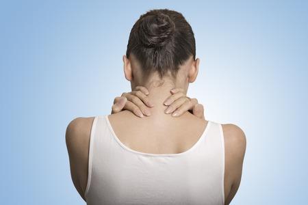 背中や背骨の病気。クローズ アップ バックアップ ビュー疲れ女性青の背景に分離された痛みを伴う首のマッサージ 写真素材