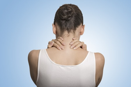 Back and spine disease. Closeup back view tired female massaging her painful neck isolated on blue background