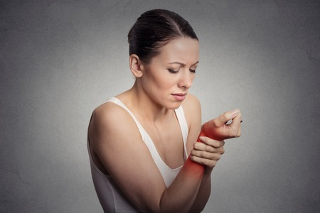 Young woman holding her painful wrist isolated on gray wall background. Sprain pain location indicated by red spot. Archivio Fotografico